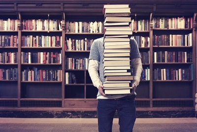 student with tall stack of books in library