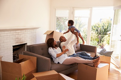 couple playing with baby surrounded by moving boxes