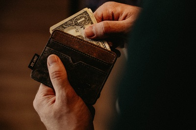man pulling cash out of wallet; photo by Allef Vinicius on Unsplash