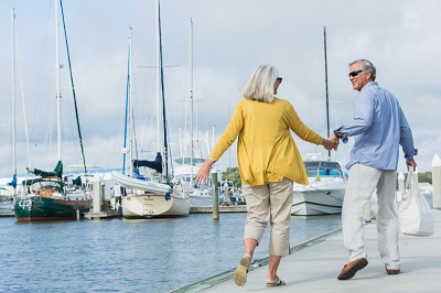 happy retired couple holding hands in a marina