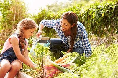 mother teaching her daughter to garden