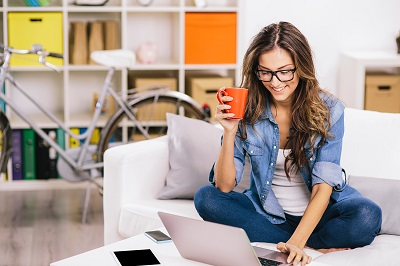 woman drinking coffee working at laptop