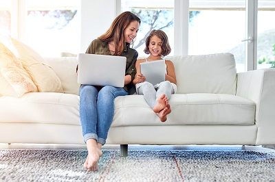 mother and daughter on sofa with laptop